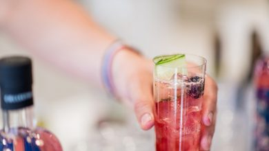 A person's hand serving a colourful drink