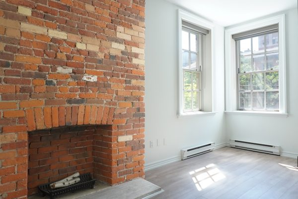 Bright windows next to a brick fireplace