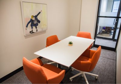 Small meeting room with orange chairs at Workplace One Bay-Bloor