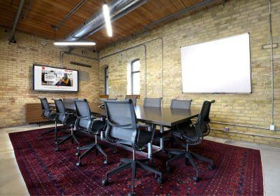 Large meeting room with brick walls and TV at Workplace One Queen