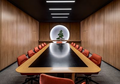 Large meeting room with orange chairs, wood walls and tree feature