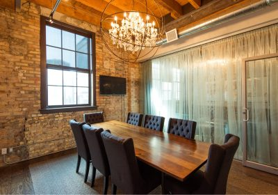 Meeting room with chandelier and brick walls at Workplace One Kitchener