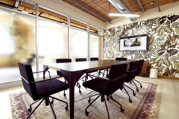 Meeting room with black chairs and floral wallpaper at Workplace One Queen